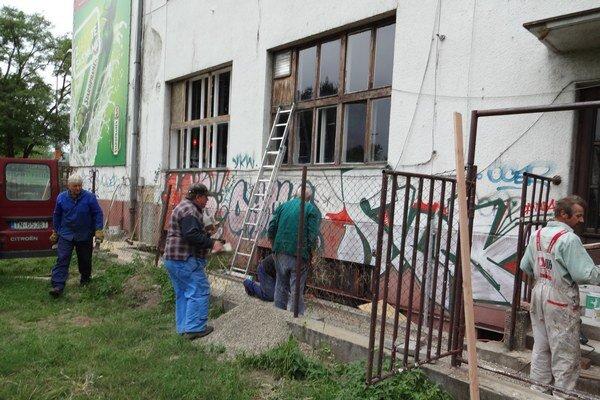 Pracovníci opravujú fasádu.