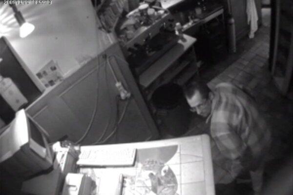 Zlodej prehľadáva priestory pod barovým pultom.