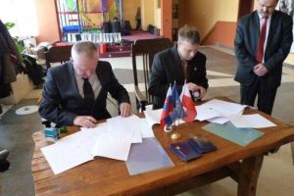 Starosta Svrčinovca Juraj Strýček (vpravo) a Piotr Trlik z Wengierskej Gorki pri podpise žiadosti predstaviteľom vlád Poľskej a Slovenskej republiky.
