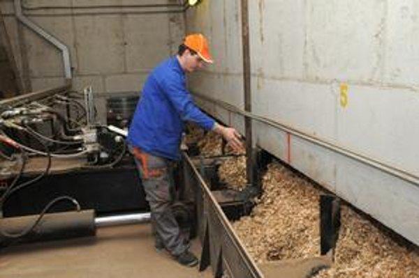 Pracovník kontroluje drevnú štiepku v kotolni na biomasu. Tá môže zásobovať teplom takmer celú Turzovku.