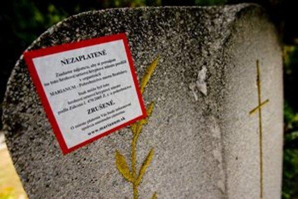 Nálepky upozorňujúce na nezaplatené hrobové miesta.