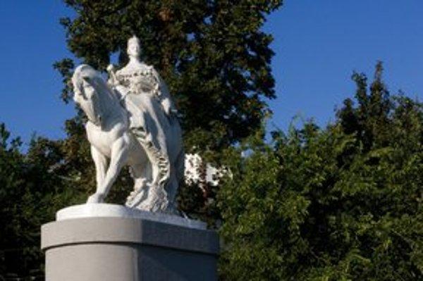 Zmenšená Mária Terézia stojí na nábreží pred národným múzeom.