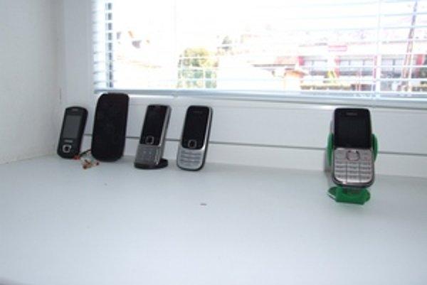 Miesto pre lepší signál. Členovia volebnej komisie v Kozelníku mali svoje mobily na okne.