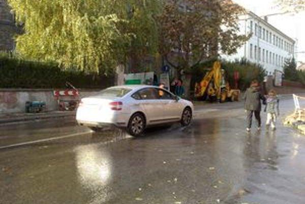 Oproti budove YMCA opravujú potrubie, voda steká na križovatku so Šancovou.