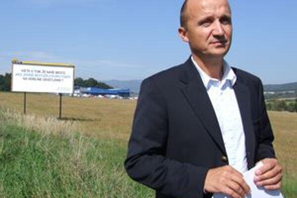Primátor Žiaru Ivan Černaj pred jedným z kontroverzných bilbordov.