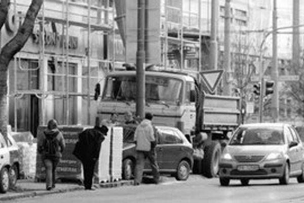 Okolo domu na ulici Mlynské nivy 1 prechádzajú chodci po ceste. Stavebník, ktorý dom opravuje, na chodníku odstavil nákladné auto a palety s tehlami.