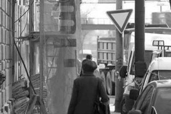 Robotníci niekedy rúrou z lešenia sypú stavebný odpad. Chodník pred domom na Mlynských Nivách 1 vtedy zatarasí kontajner.