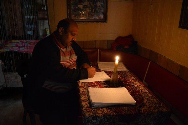 Robert Dužda pracuje večer pri sviečke. V osade, kde žije, elektrina nie je a ani nebude.