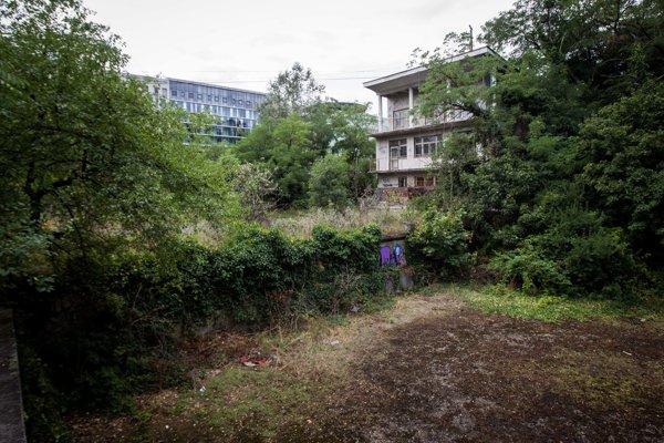 Spustnutý objekt stavby kúpaliska je v susedstve nábrežnej zóny River Park, ktorú vidno za stromami.