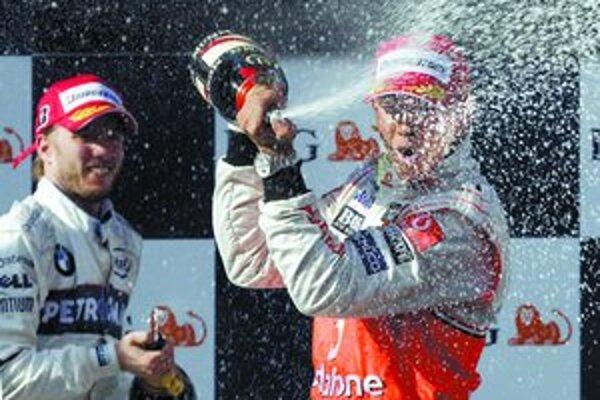 Víťaz Veľkej ceny Austrálie Lewis Hamilton z tímu McLaren oslavuje na stupni víťazov striekajúcim šampanským, vľavo je druhý v cieli Nick Heidfeld z BMW Sauber.