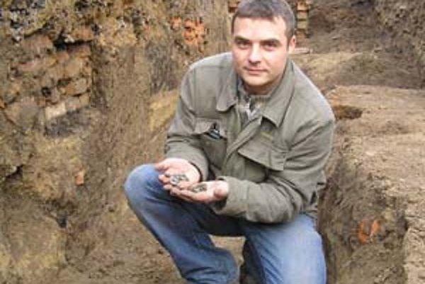 Po zaškrabnutí motykou sa z hliny vysypala hrča strieborných mincí pokrytých patinou.