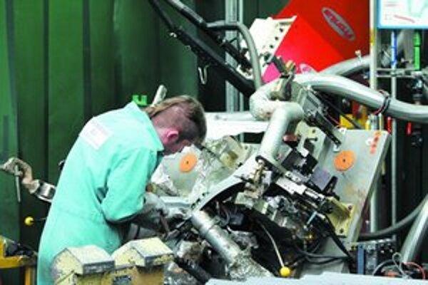 Výrobcom automobilov čoraz viac chýbajú absolventi s technickým vzdelaním. Snažia sa ich zlákať do svojich radov už počas štúdia. Na snímke pracovník v automobilke Volkswagen.