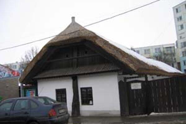 Domček so slamenou strechou stojí medzi panelákmi v Šali.