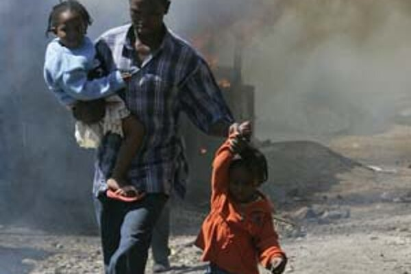 Muž uteká so svojimi deťmi pred rebelmi, ktorí podpálili budovy