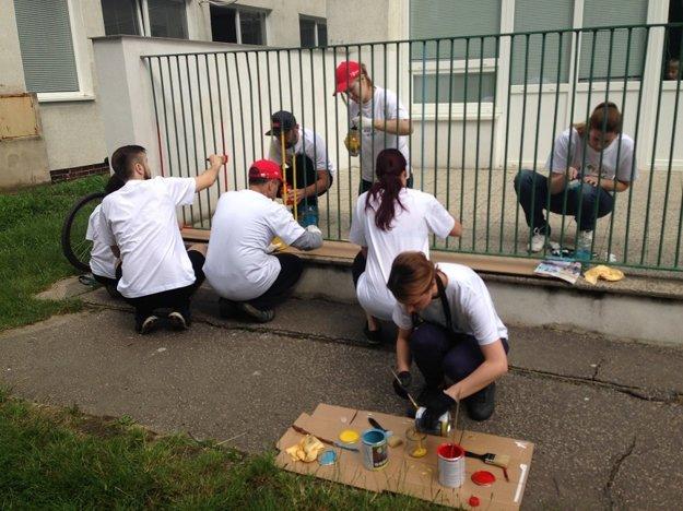 Po úprave pieskoviska sa dobrovoľníci pustili do maľovania plota.