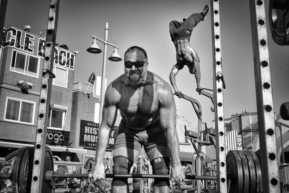 Čestné uznanie kategória Ľudia.Vzpierač na pláži.Vzpierač dvíha naloženú činku na  Venice Beach v Kalifornii, zatiaľ čo gymnasta za ním robí stojku na rukách.