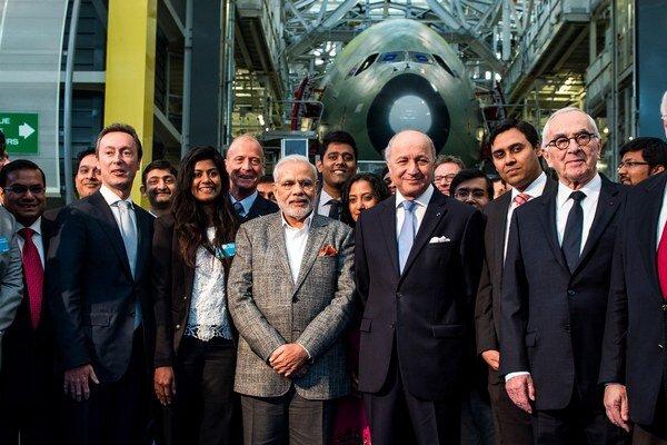 Indický premiér Nárendra Módí (uprostred vľavo), francúzsky minister zahraničných vecí Laurent Fabius (uprostred vpravo), výkonný riaditeľ Airbusu Fabrice Bregier (druhý zľava) pózujú počas návštevy vo fabrike na výrobu Airbusu A380.