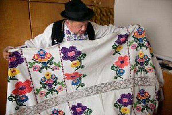 Štefan Višňovský s vyšívanou plachtou zo zbierky jeho manželky Anny Višňovskej.