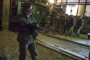 Proruský rebel stráži baníkov v bani v Donecku na východe Ukrajiny.