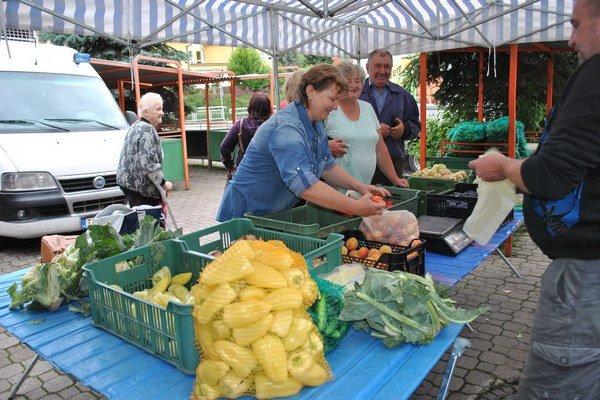 Ľudia nakupujú na trhu. O ovocie a zeleninu je veľký záujem.