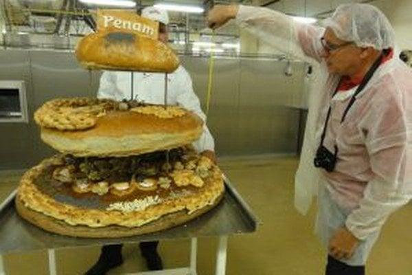 Komisár Knihy slovenských rekordov Igor Svítok premeriava rekordnú chlebovú tortu.