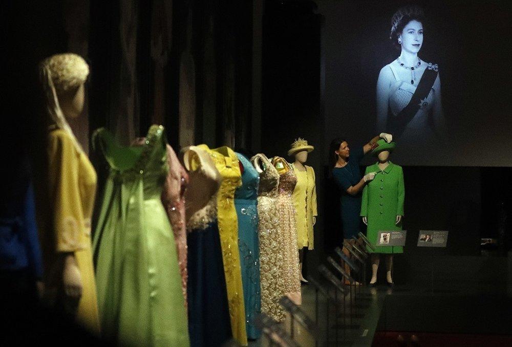 Fotografie zachytávajú Alžbetu II. spolu s vystavenými šatami, ktoré mala oblečené počas dôležitých životných míľnikov.