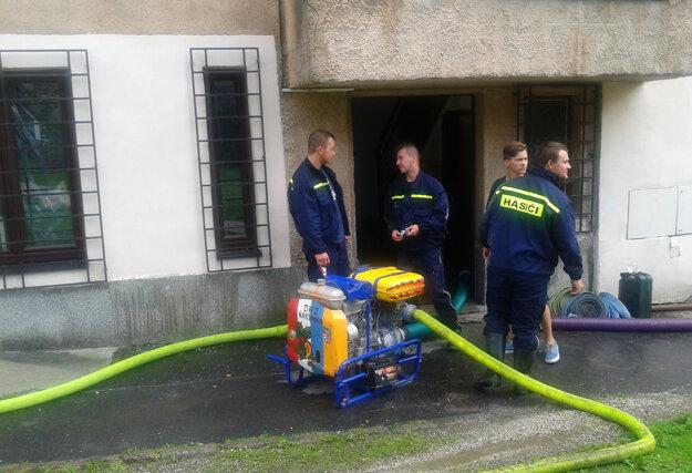 S odčerpávaním vody zo suterénu pomáhajú aj dobrovoľní hasiči.
