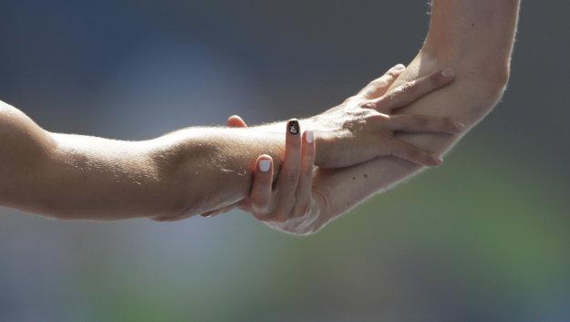 Detail rúk oboch bežkýň sa stal symbolom tohto príbehu.