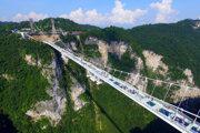 Návštevníci kráčajú po sklenenom moste v Čang-ťia-ťie (Zhangjiajie)v juhočínskej provincii Chu-nan 20. augusta 2016. Čína v sobotu oficiálne otvorila najvyšší a najdlhší visutý sklenený most, na ktorom ľudia chodia po priehľadných sklenených platniach. Stavba dlhá 430 metrov, ktorá je zavesená 300 metrov nad zemou