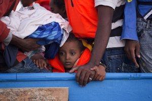 Chlapec sleduje záchrannú akciu z preplneného dreveného plavidla.