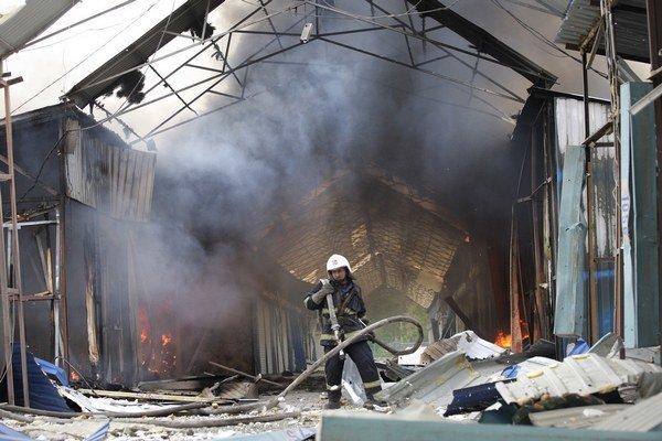 Ukrajinský hasič hasí požiar na trhovisku zničenom po ťažkom ostreľovaní v Donecku 3. júna 2015.