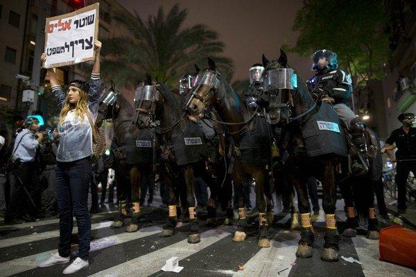 """Protestujúca drží nápis """"násilný policajt by mal byť odsúdený""""."""