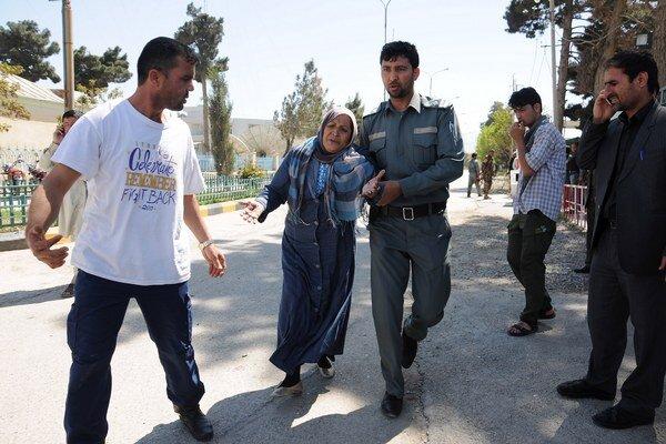 Príslušník bezpečnostných síl pomáha žene počas útoku.
