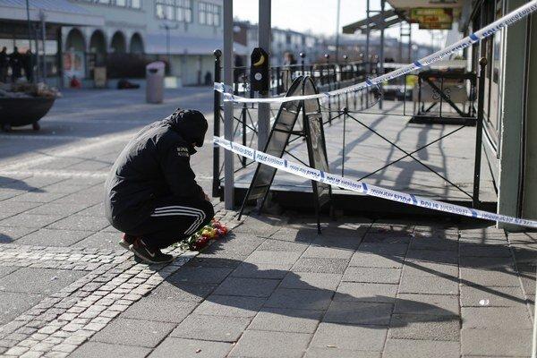 Muž kladie na chodník pred reštauráciu v Göteborgu kvety.