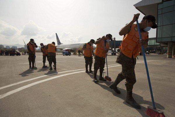 Pracovníci letiska čistia pristávacie dráhy od popola, ktorý chrlí sopka Fuego.