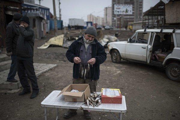 Muž predáva ryby na trhu v Mariupoli, štyri dni po útoku na mesto.