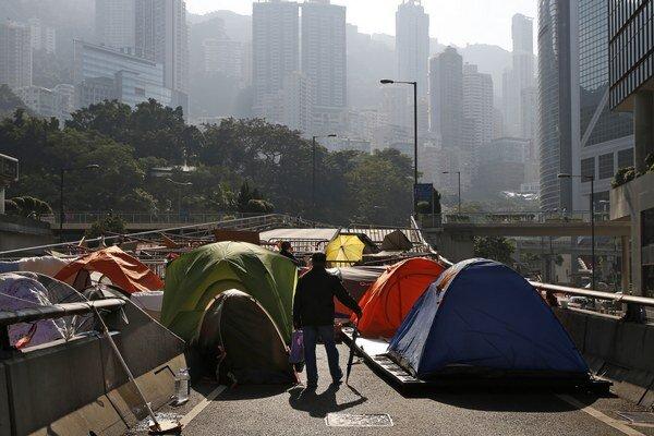 Starší muž kráča pomedzi stany prodemokratických demonštrantov v okupovanej oblasti pred vládnym sídlom v štvrti Admiralty v Hongkongu.