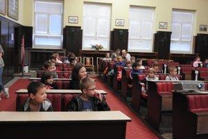 Deti si zasadli do lavíc, v ktorých sedia počas rokovaní mestskí poslanci.