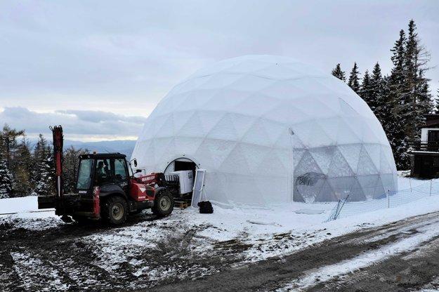 Traktor priváža kváder ľadu do krytej kupoly  počas výstavby Ľadového dómu.