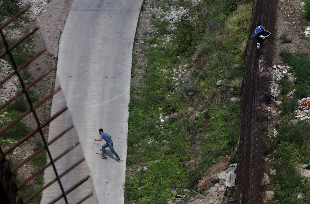 Dvaja muži utekajú cez hranicu. FOTO – SITA/AP