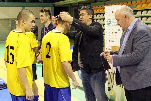 Na minulom ročníku sa z prvenstva tešili dorastenci Ivanky. Na snímke im blahoželajú Pavol Šlosár zo spoločnosti PP Invest a Štefan Korman, predseda ObFZ.