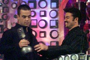 Britský spevák Robbie Williams (vľavo) preberá z rúk Georga Michaela    cenu hudobnej stanice MTV, ktorú mu udelili v kategórii najlepší spevák  12. novembra 1998 v Miláne.