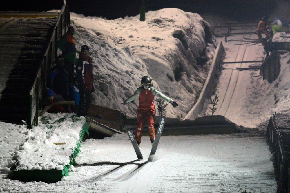 Mladý skokan na lyžiach počas tréningu.