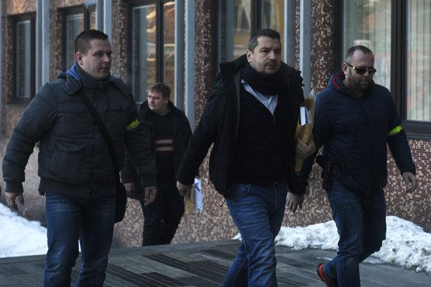 Policajti z Národnej kriminálnej agentúry (NAKA) doprevádzajú advokáta Viktora Križiaka (uprostred) na okresný súd v Trenčíne.