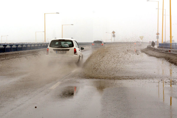 Voda na ceste. Roztopený sneh pokryl cesty vodou.