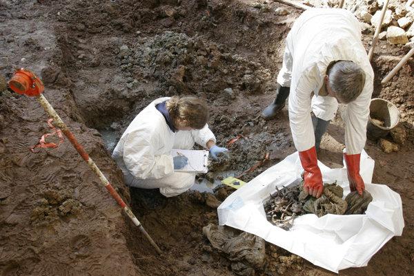 Forenzný experti zbierajú dôkazy v masovom hrobe (ilustračné foto).