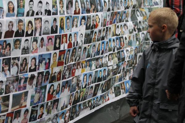 Chlapec sa pozerá na fotografie obetí útoku v Beslane.