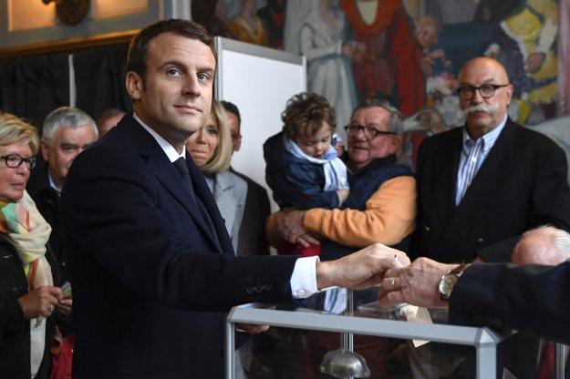 Francúzsky prezidentský kandidát Emmanuel Macron vhadzuje obálku do urny v 1. kole prezidentských volieb.