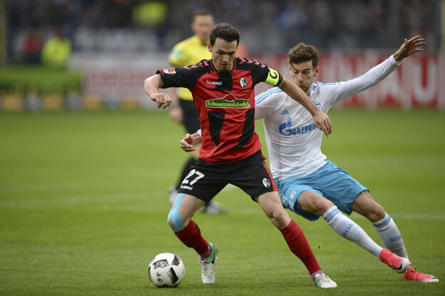 Nicolas Hoefler (vľavo) z Freiburgu si kryje loptu pred Leonom Goretzkom zo Schalke.