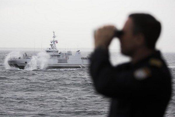 Nórsky námorník pozerá cez ďalekohľad na lodi v Baltskom mori.
